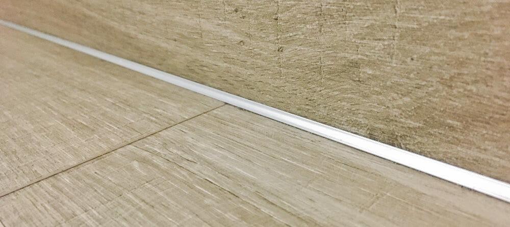 Detail vnútorného rohu na schodisku pokrytom lepenou vinylovou podlahou.