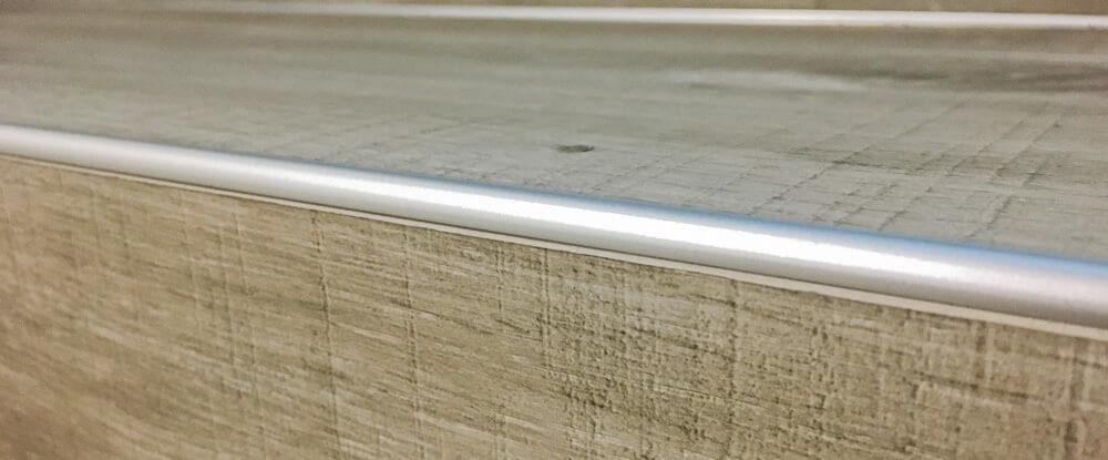 Detail hliníkovej schodovej hrany na schodisku pokrytom lepenou vinylovou podlahou